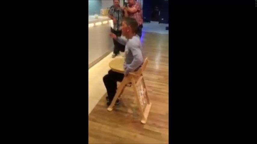 Un chico se sienta en una silla de bebé y luego no puede salir de ella