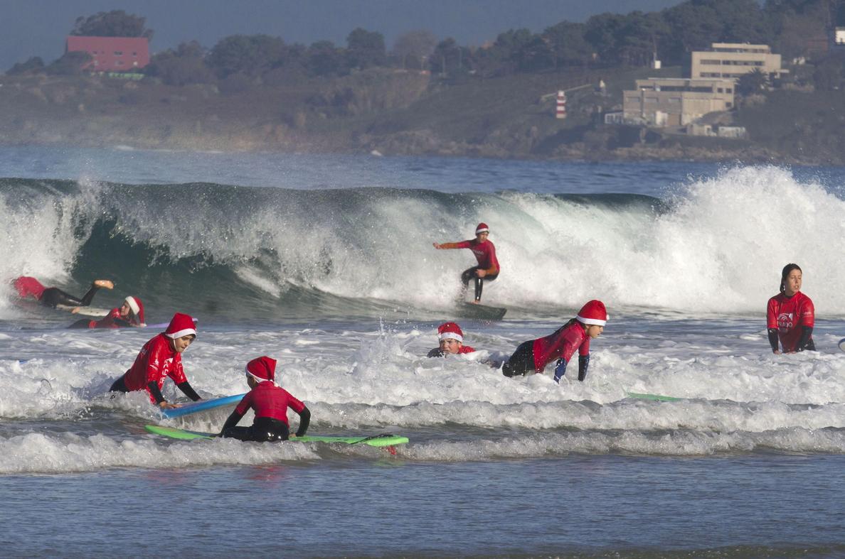 Papá Noel surfea las olas de la playa gallega de Patos