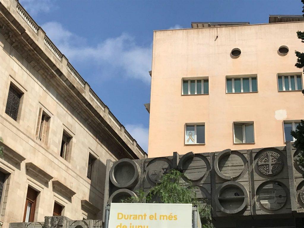 Alberto Fernández (PP) cuelga un lazo con la bandera española y catalana en la ventana de su despacho